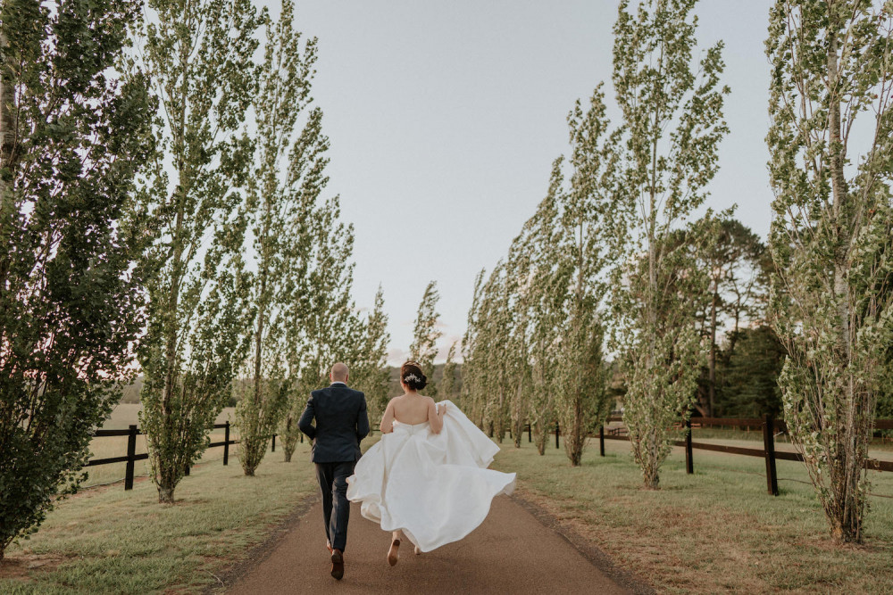 Bride and groom running down a path together