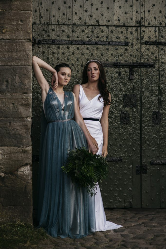 Two bridal models posing outside castle at night. The wedding dresses are in silver, white and blue worn with smokey eyes and glowing complexion. One bride wears hair down with a pretty tiara. Bride in blue dress holds a wild foliage flowerless bouquet