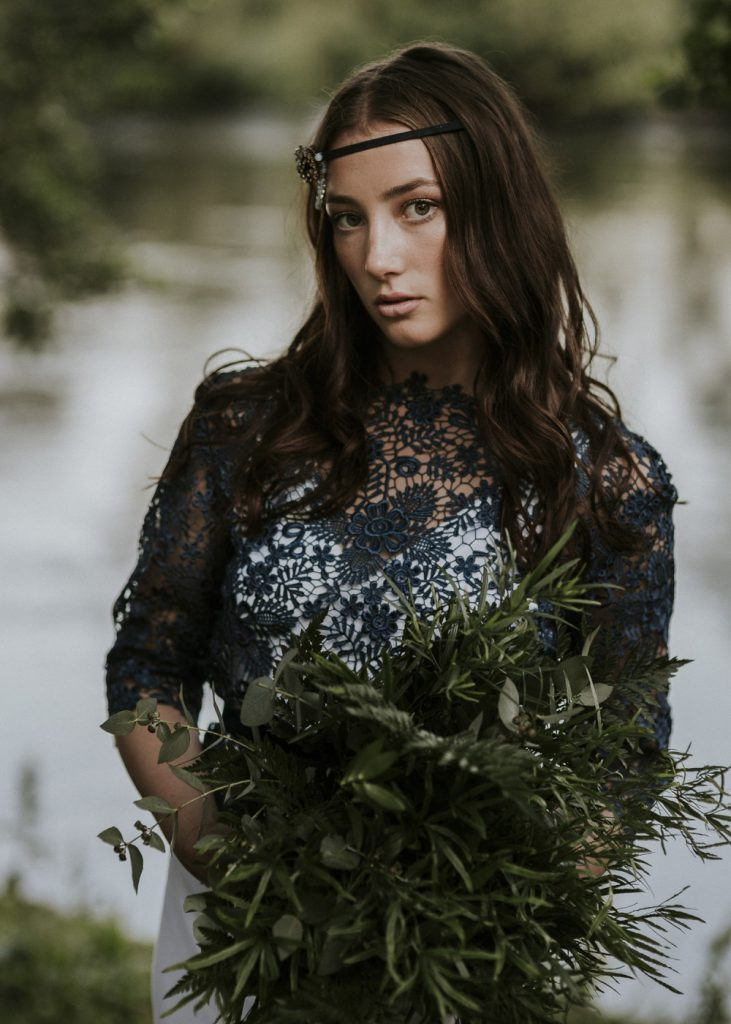 Brunette bride wearing navy blue long sleeve lace top and holding a wild foliage bouquet