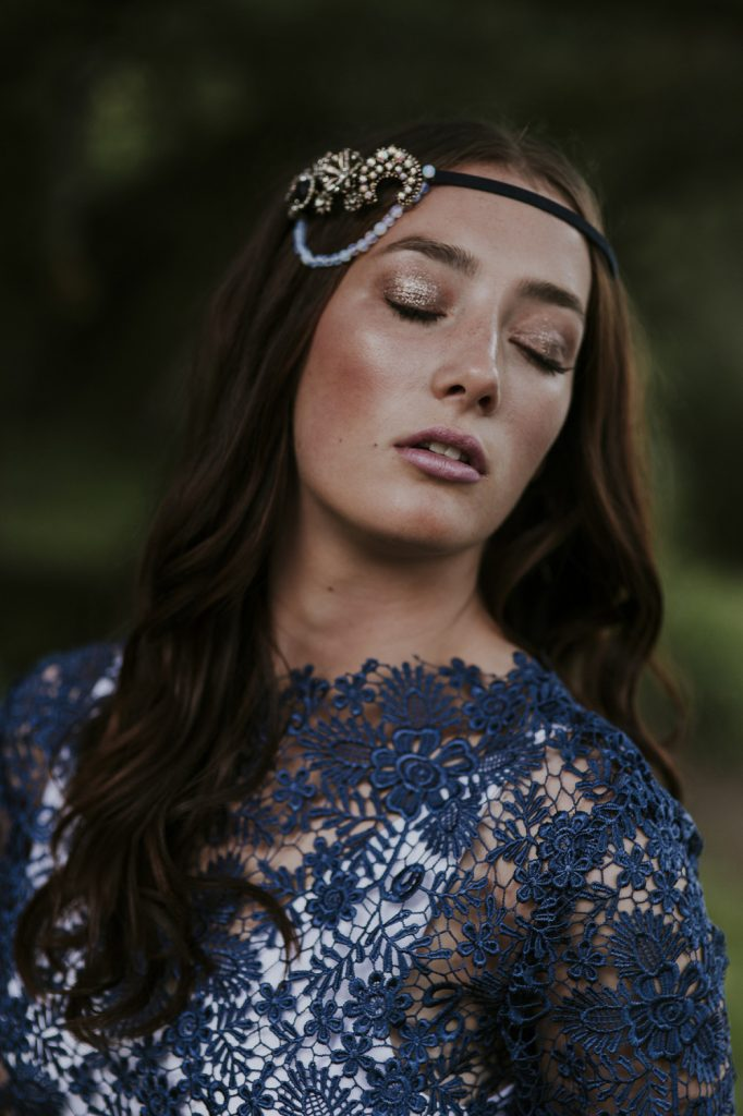Brunette bride wearing navy blue long sleeve lace top worn with pink lipstick and sparkly gold metallic eyeshadow