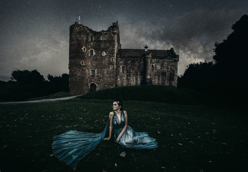 Beautiful bride  in blue wedding dress sitting in front of a Castle at night with dark stormy skies.