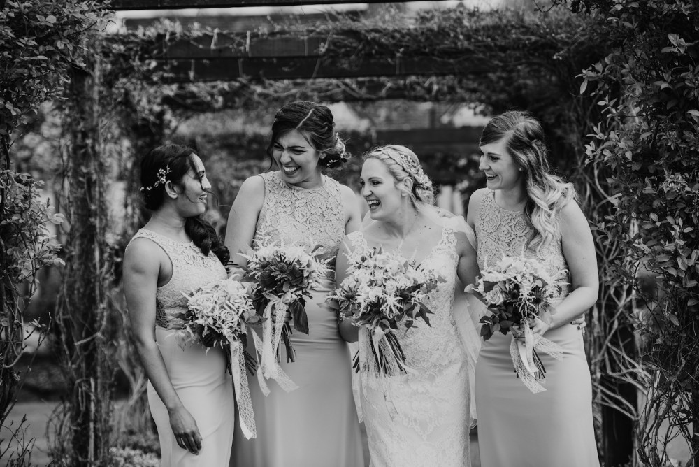Black and white image of bride and bridesmaids laughing