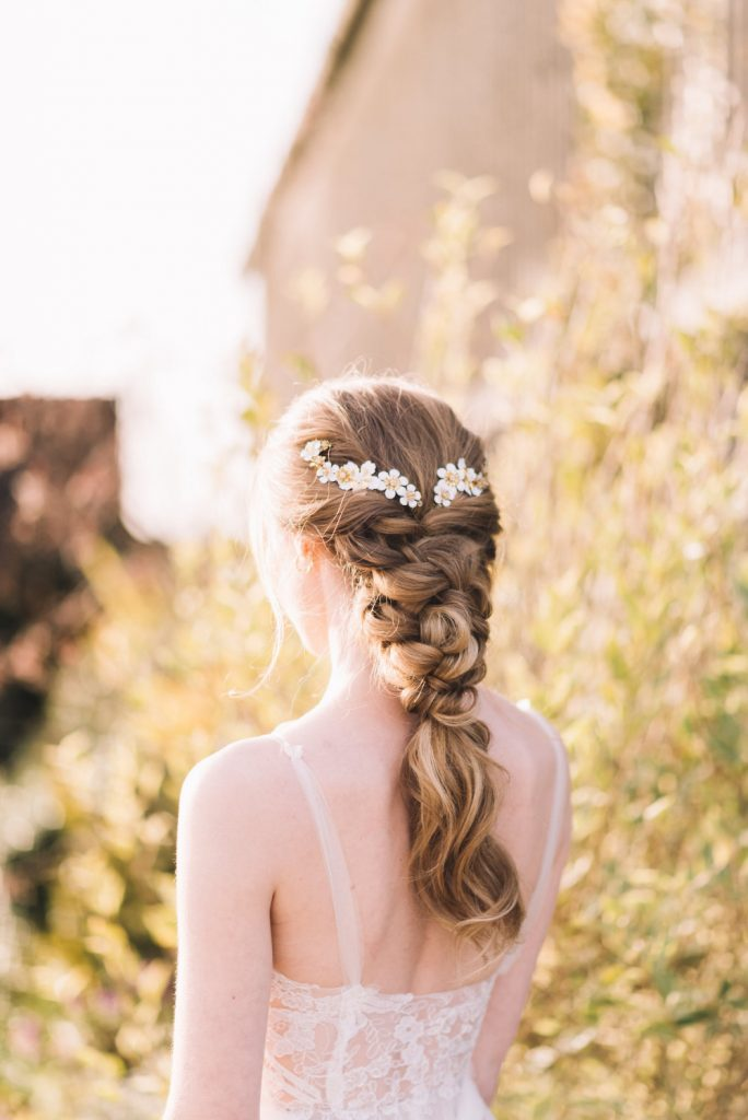 Bride with blonde hair worn in chunky plait with daisy bridal hair pins