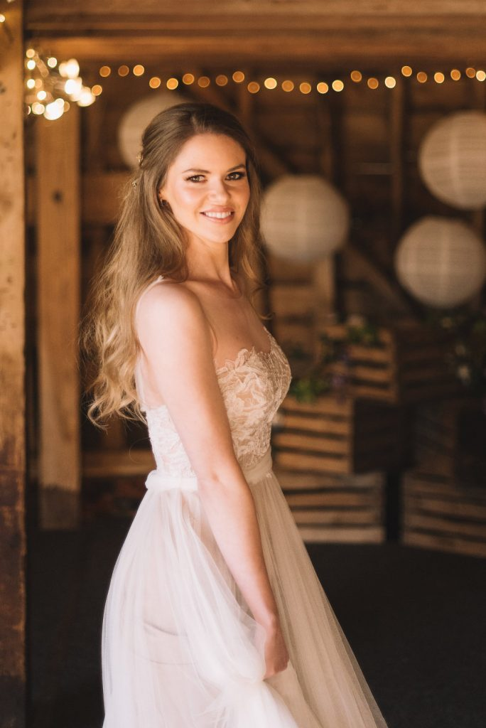 Bride smiling and dancing in lace wedding dress in a barn with fairylights and sunlight on her face. Hair worn in a soft half up bridal hairstyle with pretty hair pins