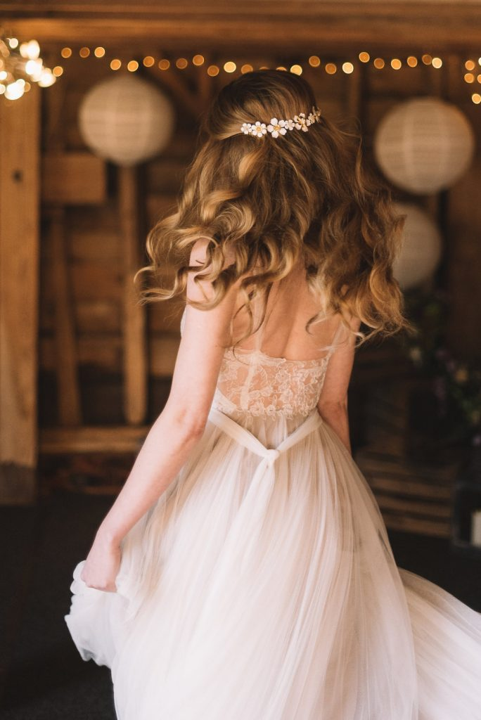 Bride smiling and dancing in lace wedding dress in a barn with fairylights and sunlight on her face. Hair worn in a soft half up bridal hairstyle with pretty daisy hair clip