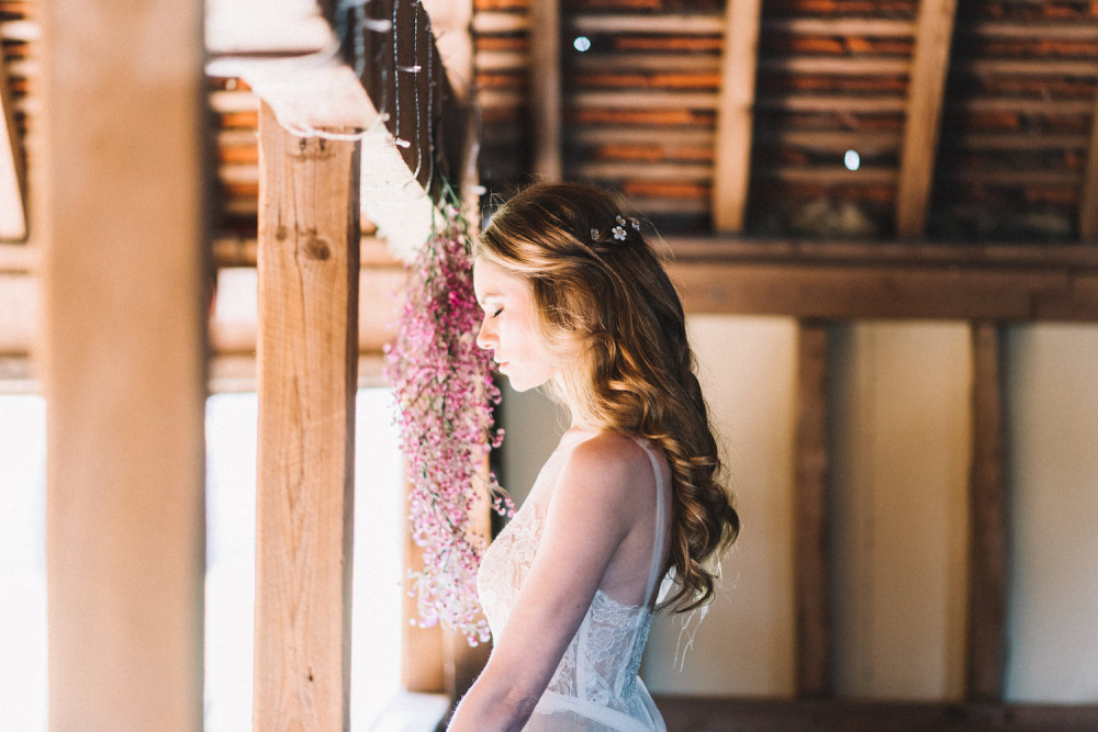Bride in barn with eye closed in the sunlight. Hair worn in soft half up bridal hairstyle with pretty dairy hair accessory