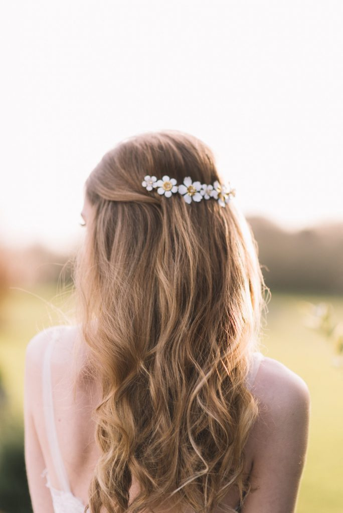 Blonde hair bride with half up hairstyle and daisy hair clip