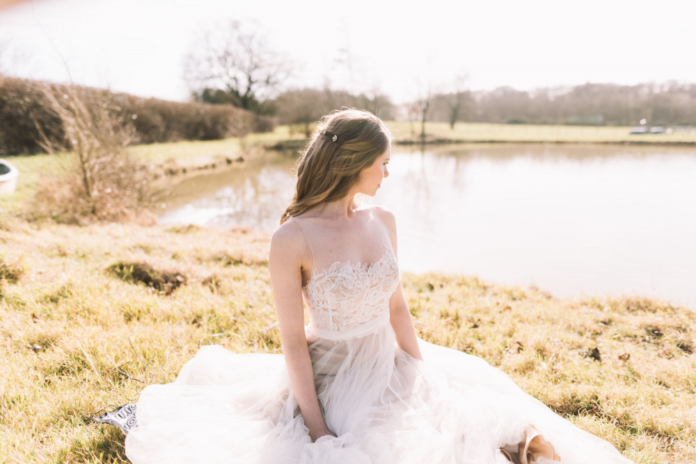 Blonde hair bride with half up hairstyle and daisy hair clip sitting by lake in the sunshine
