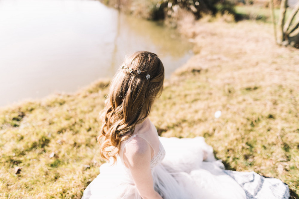 Blonde hair bride with half up hairstyle and daisy hair pins sitting by lake in the sunshine