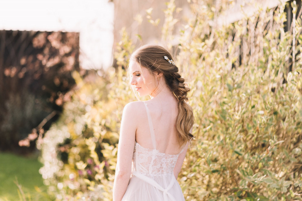 Bride with blonde hair worn in chunky plait, standing in sunshine