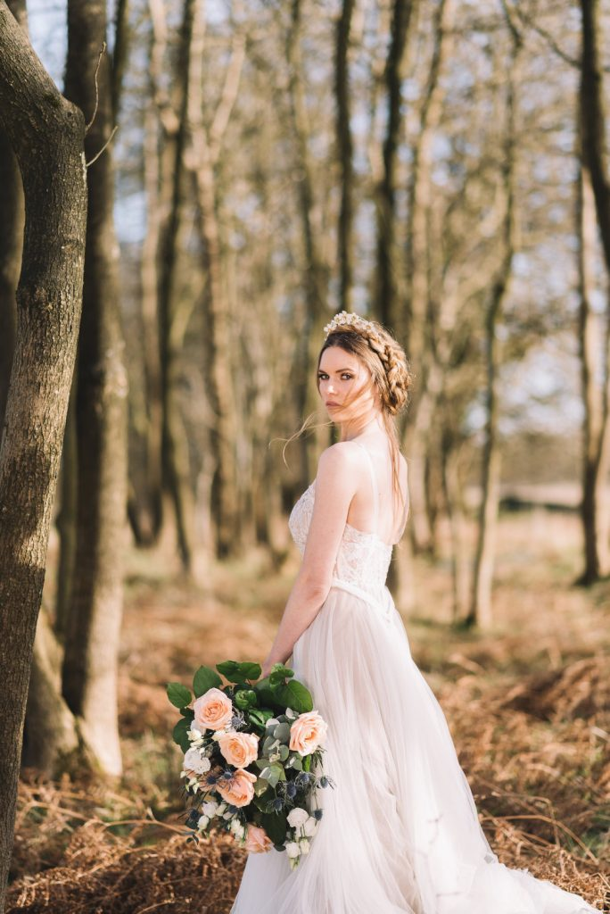 Beautiful bride in woods wearing flowing wedding dress with hair up in crown braid and holding white and peach flower bouquet