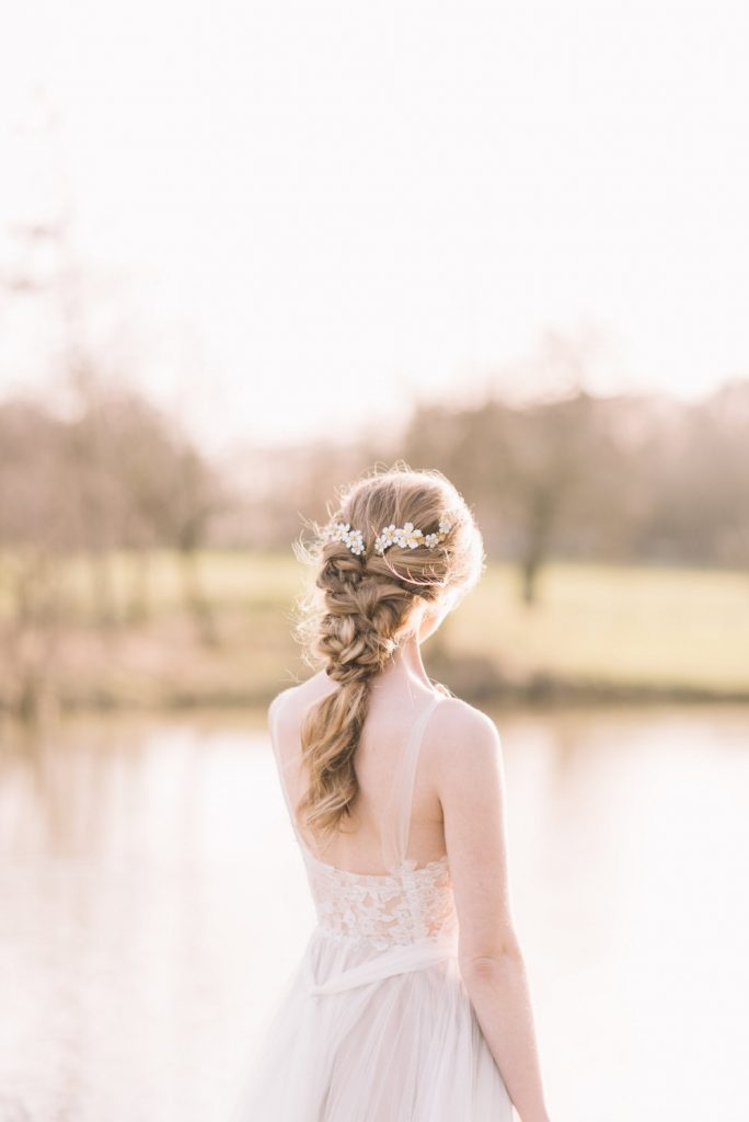 Bride standing in sunshine by a lake with beautiful blonde hair worn in chunky boho plait with daisy bridal hair pins