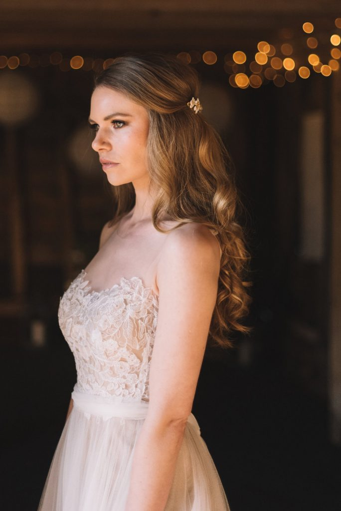 Bride in lace wedding dress standing in barn with fairylights and sunlight on her face. Hair worn in a soft half up bridal hairstyle with pretty hair pins