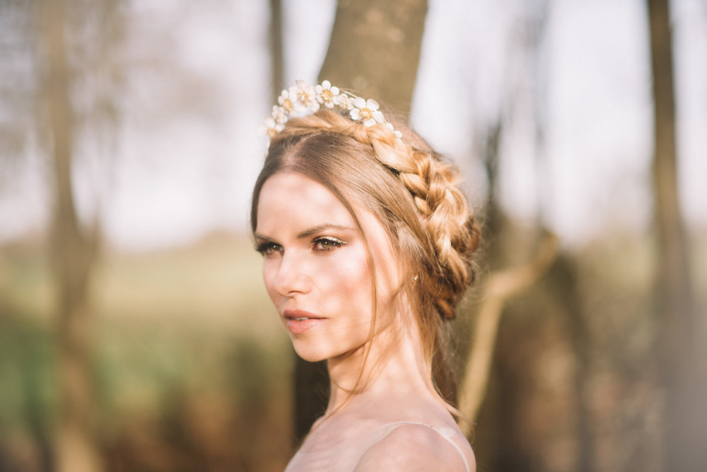 Bride in woods with sunlight on her face wearing Dutch crown braid and flower tiara.