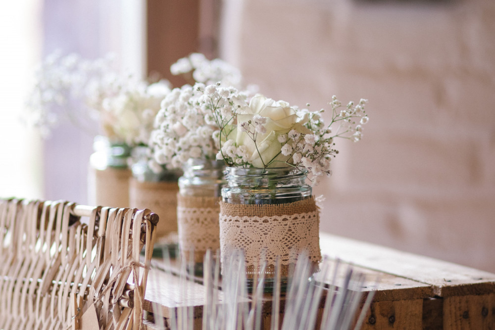 Rustic wedding flowers with gypsophila and white roses, candles and jars