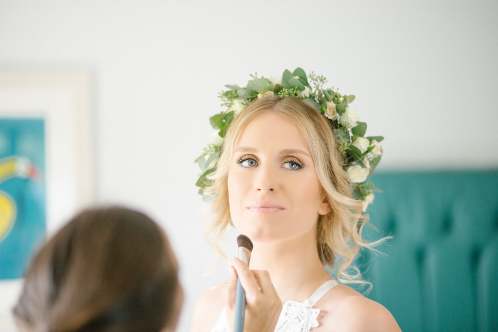 Beautiful bride having makeup finishing touches