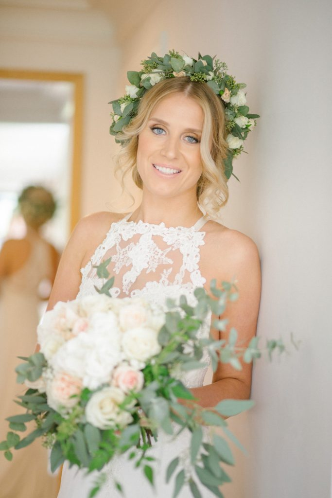 Beautiful boho bride hair and makeup with flowers in hair and matching flowers in hands