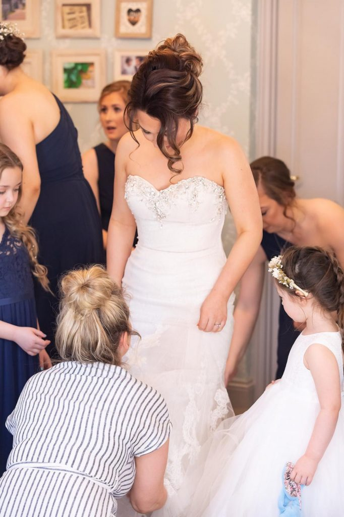 Bridesmaids helping the bride get into her wedding dress