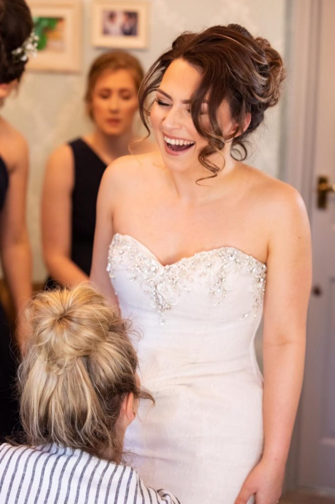 Bride laughing as she is getting ready