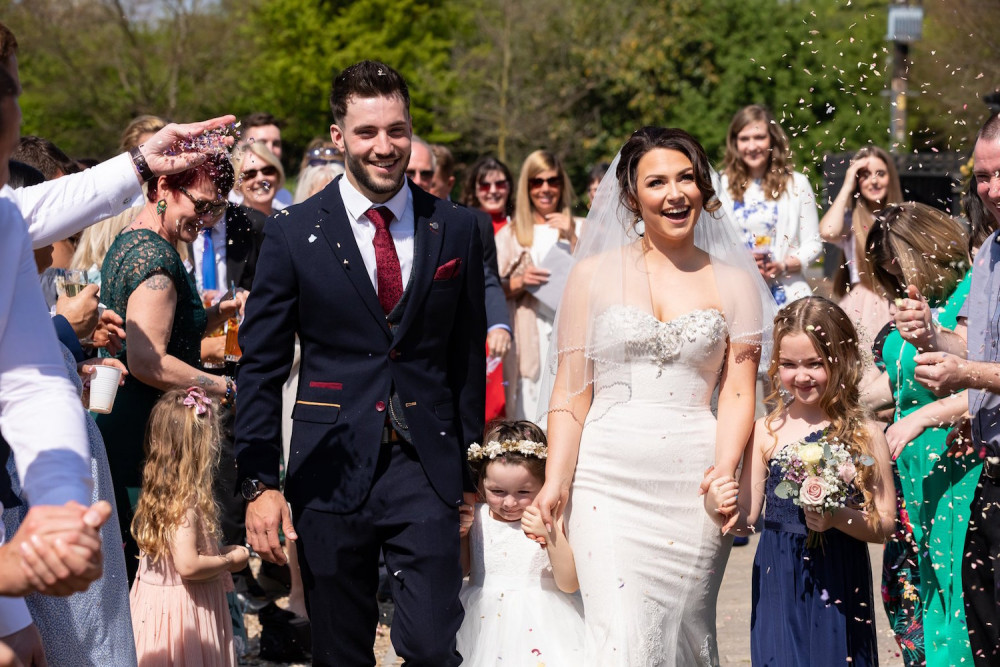 Bride and groom walking and having confetti thrown over them
