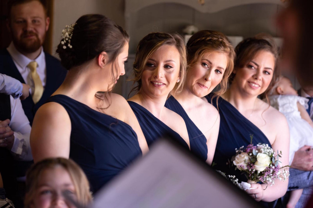 Bridesmaids smiling with each other in blue dresses holding flowers