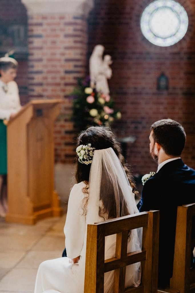 Bride and groom seated during church wedding ceremony