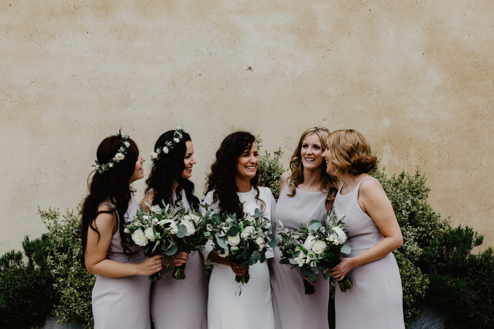 Laughing bride with her beautiful bridesmaids wearing lilac dresses