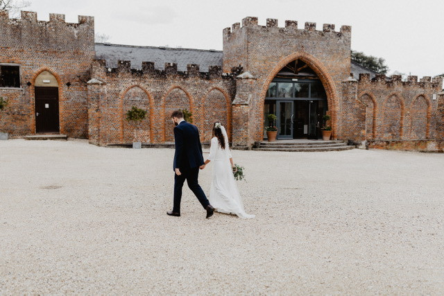 Bride and groom walking into wedding venue