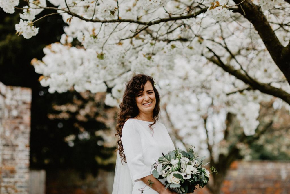 Beautiful brunette bride with curly hair holding green and white bouquet standing by cherry blossom tree