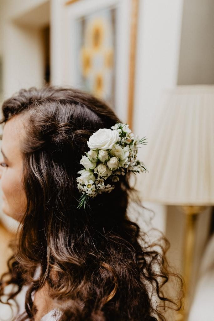 Brunette curly haired bride with white roses in hair