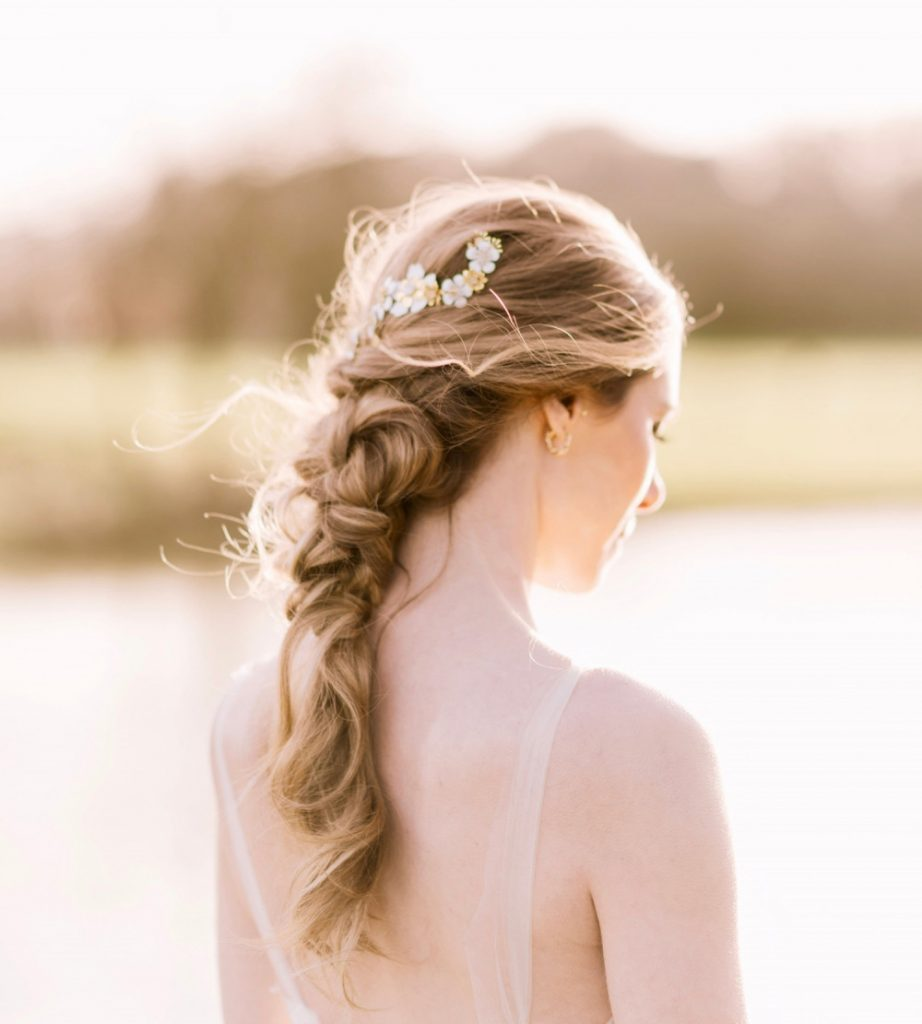 Chunky knotted plait with white floral hair clip on beautiful bride standing by a lake in the sunshine