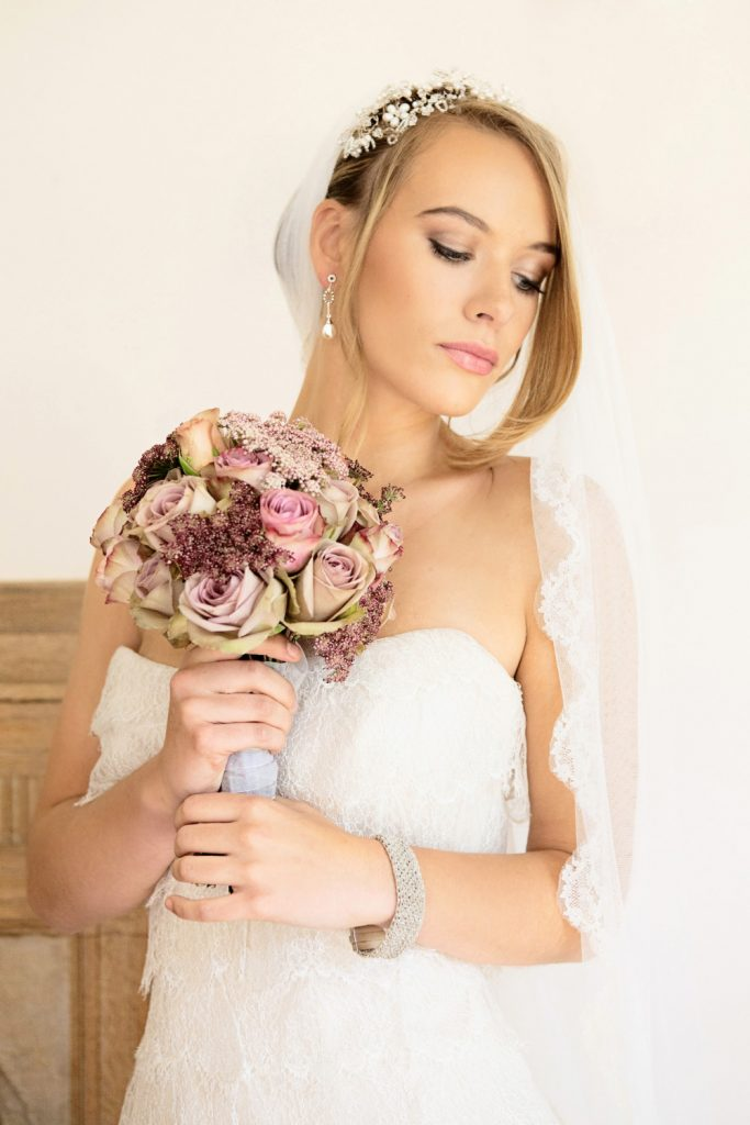Beautiful bride wearing fingertip length veil. Makeup by Powder and Paint Photography by Melanie East