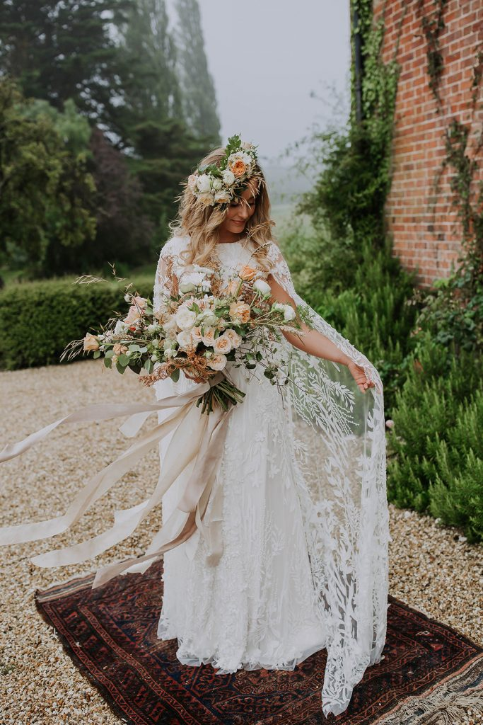 elegant-boho-bride-with-lace-cape-wedding-dress-and-floral-crown