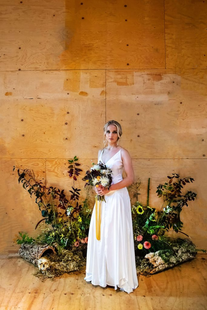 bride-with-floral-ceremony-backdrop