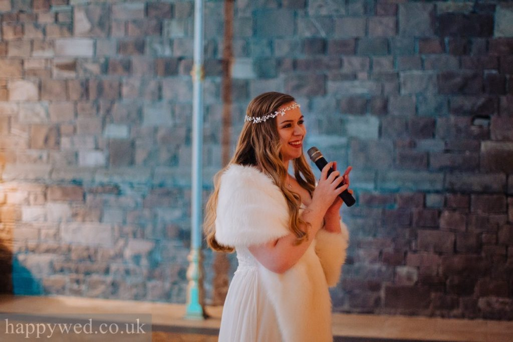 bride in fur stole singing to groom
