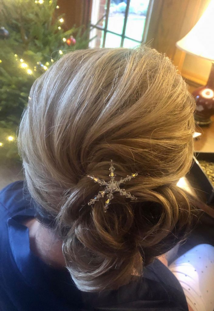 bridesmaid winter wedding updo side bun with crystal snowflake detail