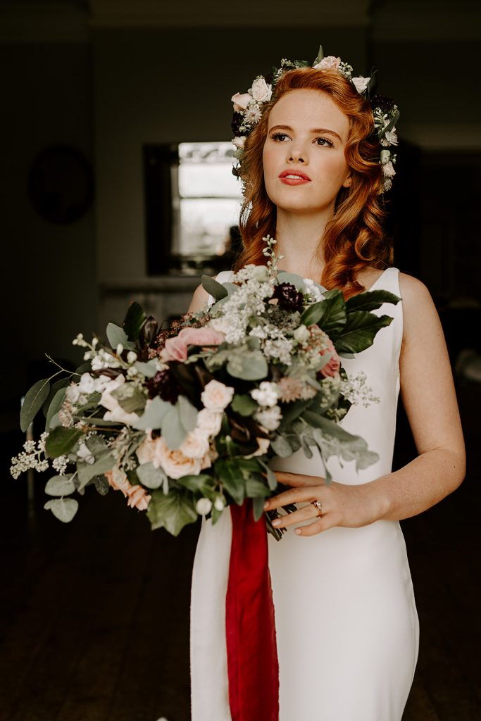bride with loose floral bouquet and flower crown